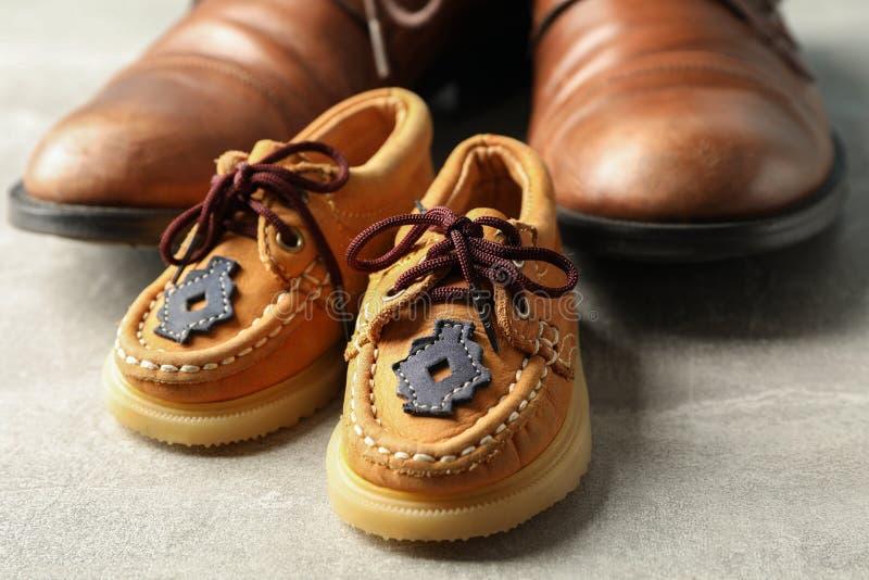 Scarpe di cuoio di Brown e le scarpe dei bambini su fondo grigio, spazio per testo fotografia stock libera da diritti