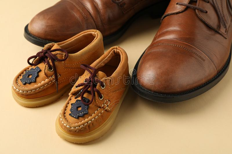 Scarpe di cuoio di Brown e le scarpe dei bambini sul fondo di colore, spazio per testo fotografia stock libera da diritti