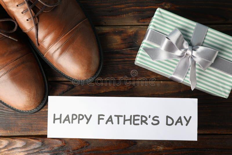 Scarpe di cuoio di Brown, giorno di padri felice dell'iscrizione e contenitore di regalo su fondo di legno, spazio per testo immagine stock libera da diritti