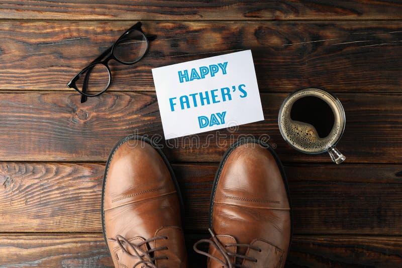 Scarpe di cuoio di Brown, giorno di padri felice dell'iscrizione, tazza di caffè e vetri su fondo di legno, spazio per testo fotografie stock