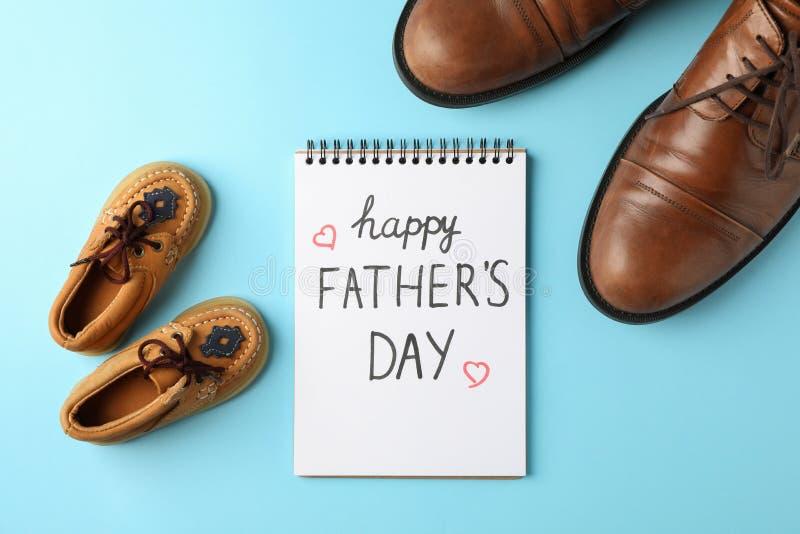 Scarpe di cuoio di Brown, le scarpe dei bambini e taccuino con il giorno di padri felice dell'iscrizione sul fondo di colore fotografie stock libere da diritti