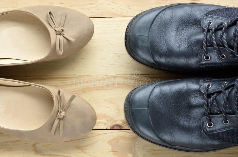 Scarpe di cuoio nere dell'uomo di fronte alle scarpe beige eleganti di una donna fotografie stock libere da diritti