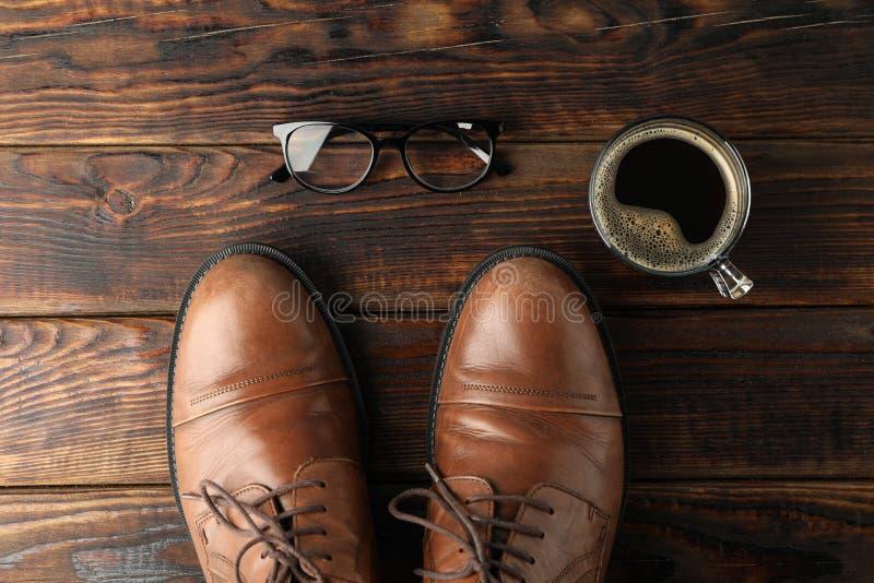Scarpe di cuoio, tazza di caffè e vetri di Brown su fondo di legno, spazio per testo fotografia stock