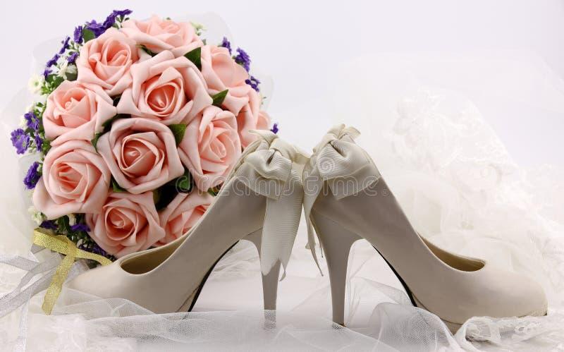 Scarpe di nozze e fiori della tenuta fotografia stock libera da diritti
