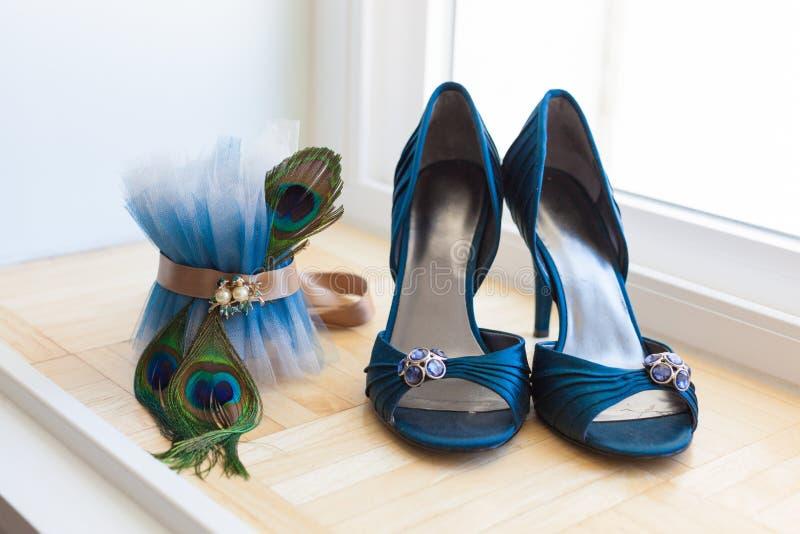 Scarpe di nozze e giarrettiera del pavone immagine stock