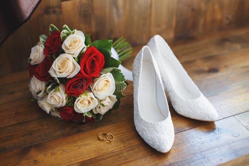 Scarpe di nozze e mazzo delle rose rosse e bianche immagini stock libere da diritti