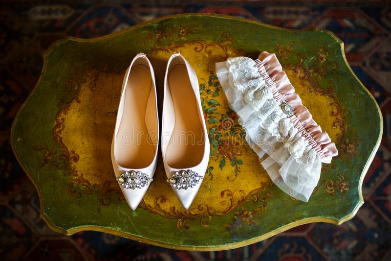 Scarpe di nozze sulla tavola d'annata e sulla giarrettiera nuziale fotografie stock
