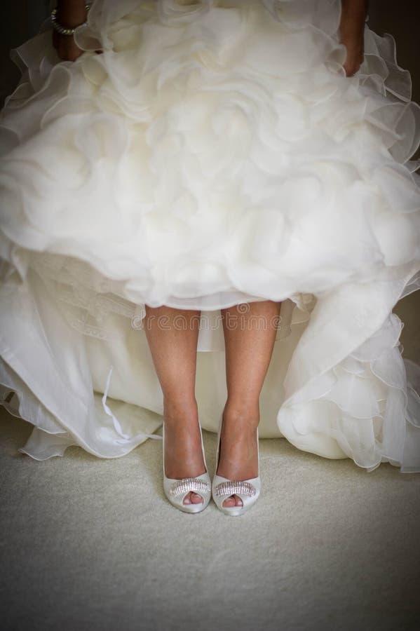 Scarpe e gambe della sposa fotografia stock