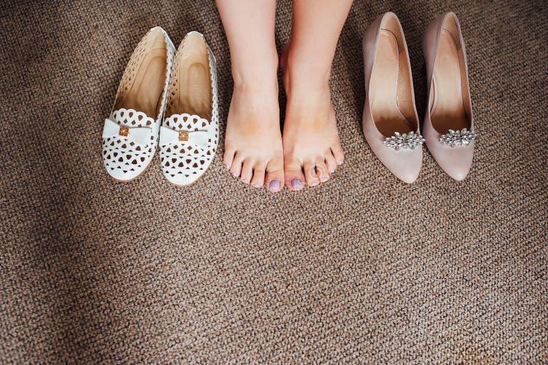 Scarpe e gambe della sposa sul pavimento immagini stock libere da diritti
