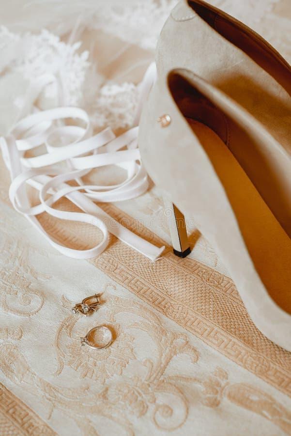 Scarpe e gioiello di lusso della sposa sul letto Fine in su fotografia stock libera da diritti