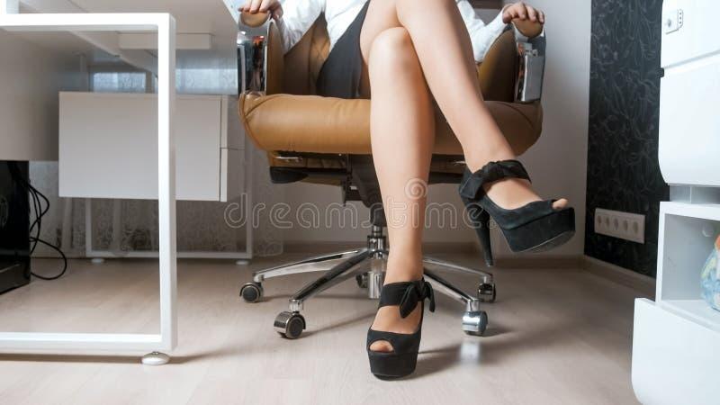 Scarpe e minigonna d'uso dei tacchi alti della giovane donna sexy che si siedono nella sedia dell'ufficio fotografia stock libera da diritti