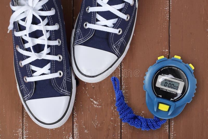 Scarpe e sport dei vestiti - gumshoes blu di paia del frammento di vista superiore e fondo di legno del cronometro fotografia stock