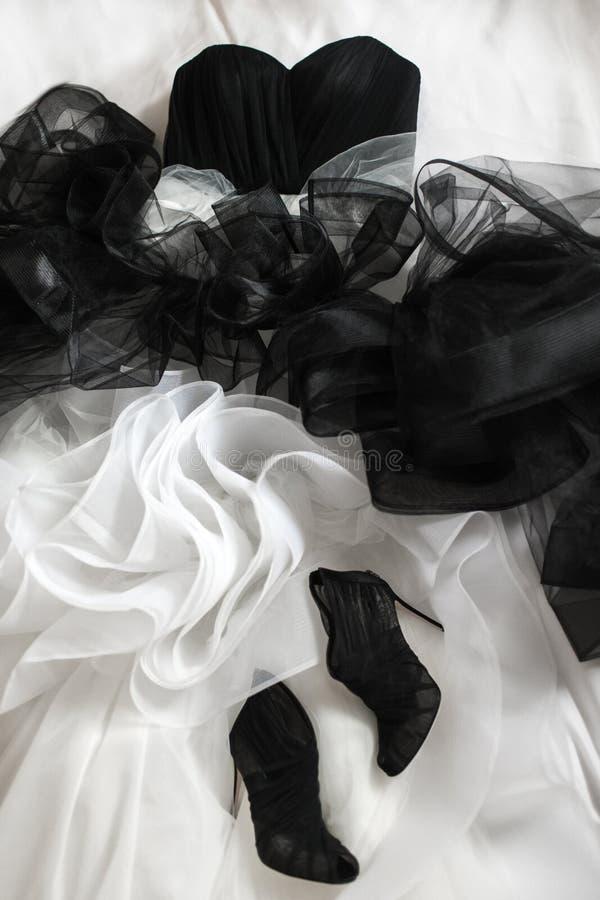 Scarpe e vestito da sposa di nozze sul letto immagine stock
