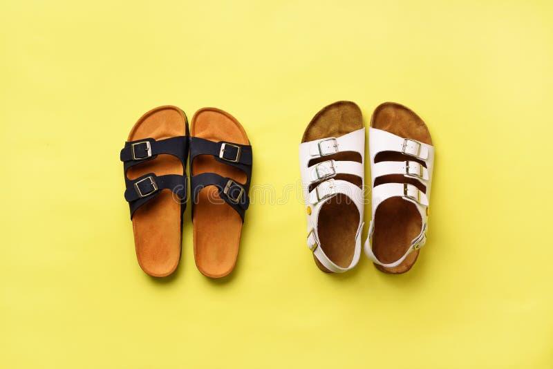 Scarpe femminili di estate - birkenstock e pantofole dei sandali su fondo giallo con lo spazio della copia Vista superiore Piano  immagine stock libera da diritti
