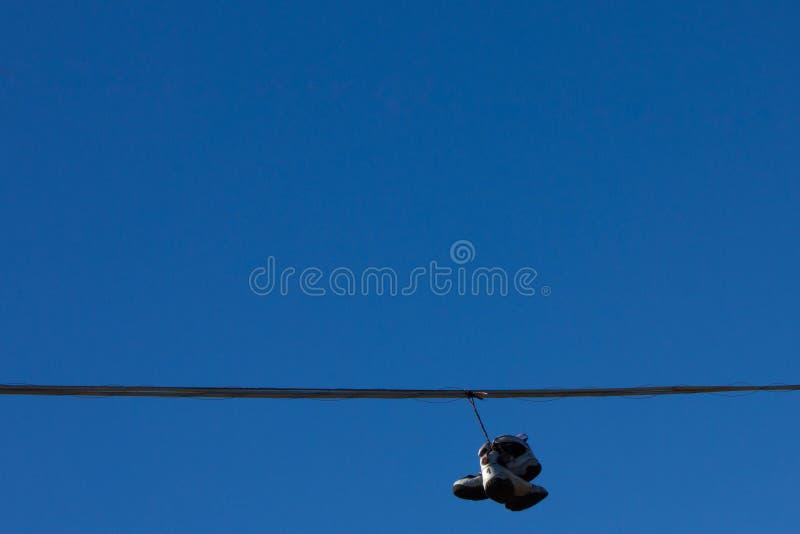 Scarpe gettate sulla linea elettrica immagini stock