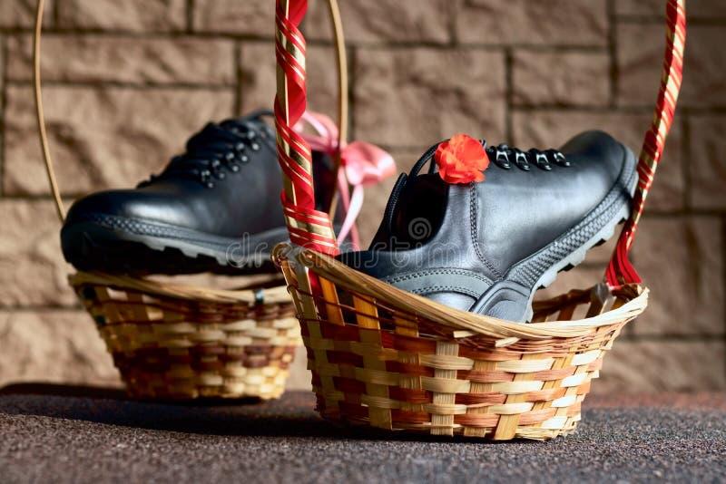 Scarpe nere d'autunno in cuoio con cestini di vimini e decorate con un geranio di fiore rosso, presentate come un regalo per prot immagini stock libere da diritti