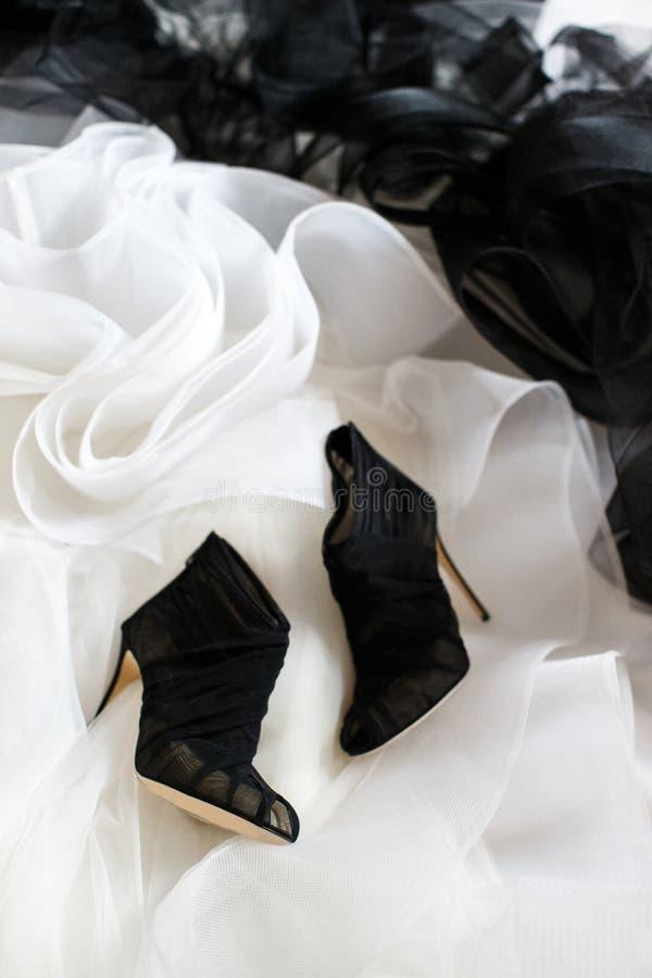 Scarpe nere di nozze su un vestito da sposa fotografie stock libere da diritti
