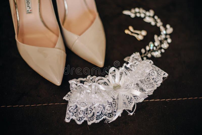 Scarpe a tacco alto con l'ornamento e la fasciatura dei capelli degli orecchini per il ` s della sposa fotografia stock