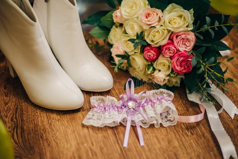 Scarpe a tacco alto del ` s delle donne bianche con una fasciatura sul piede e un mazzo di nozze per la sposa fotografia stock libera da diritti