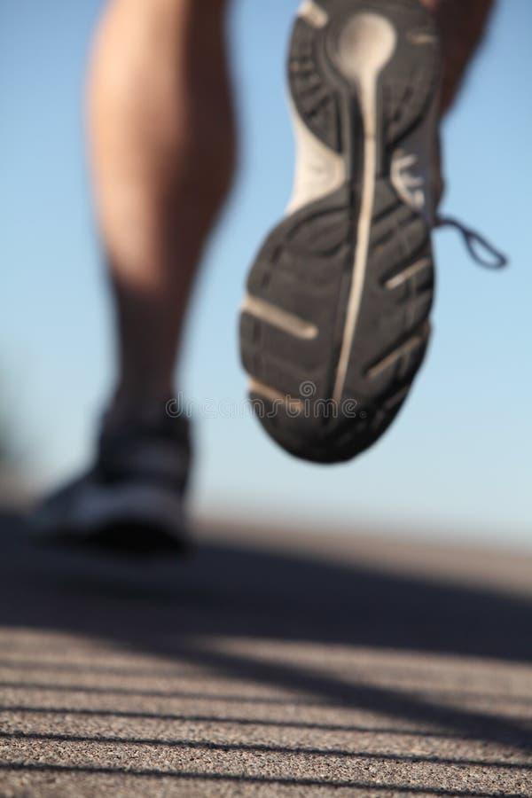 Scarpe Unfocused dell'uomo che funzionano sull'asfalto immagine stock libera da diritti