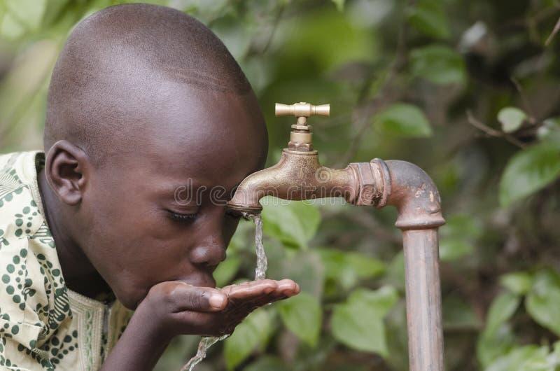 Scarsity da água no símbolo do mundo Menino africano que implora pelo wate fotografia de stock royalty free