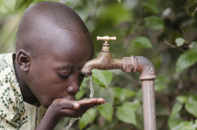 Scarsity de l'eau dans le symbole du monde Garçon africain priant pour le wate photographie stock libre de droits