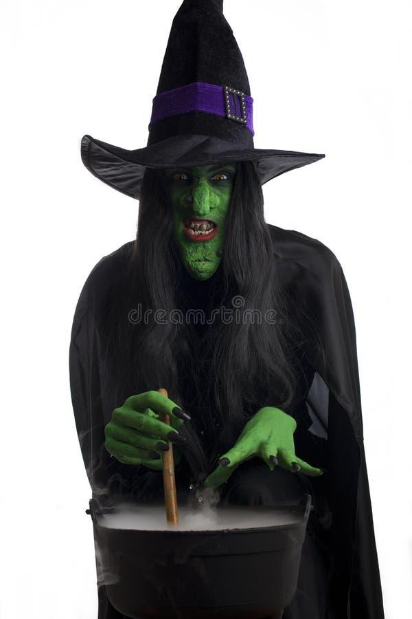 Scary μάγισσα που ανακατώνει το καζάνι της στοκ φωτογραφία