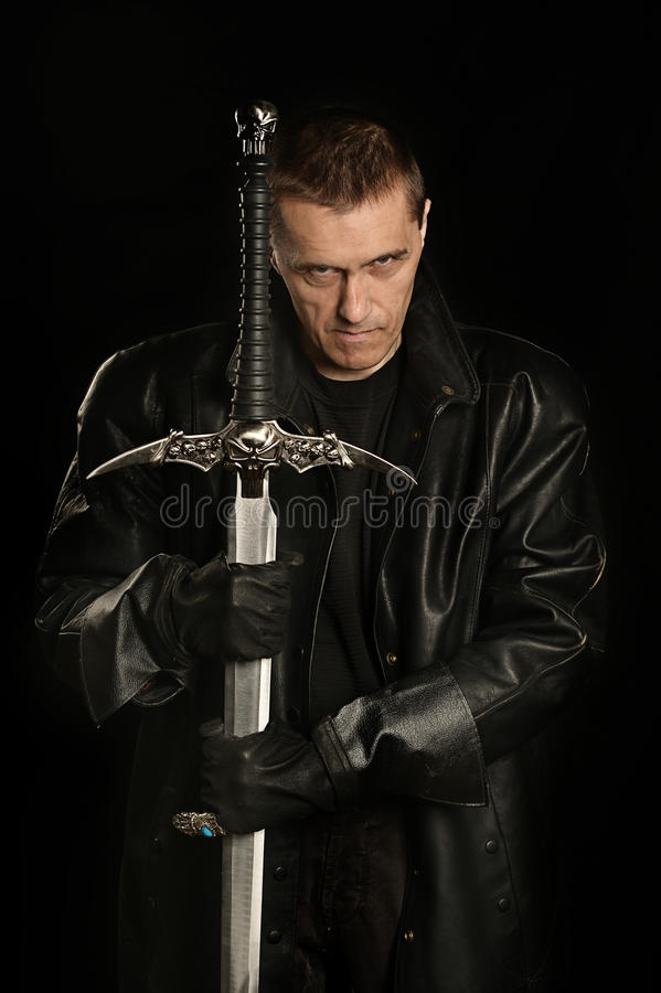 Scary assassin with sword. Over dark background royalty free stock photos