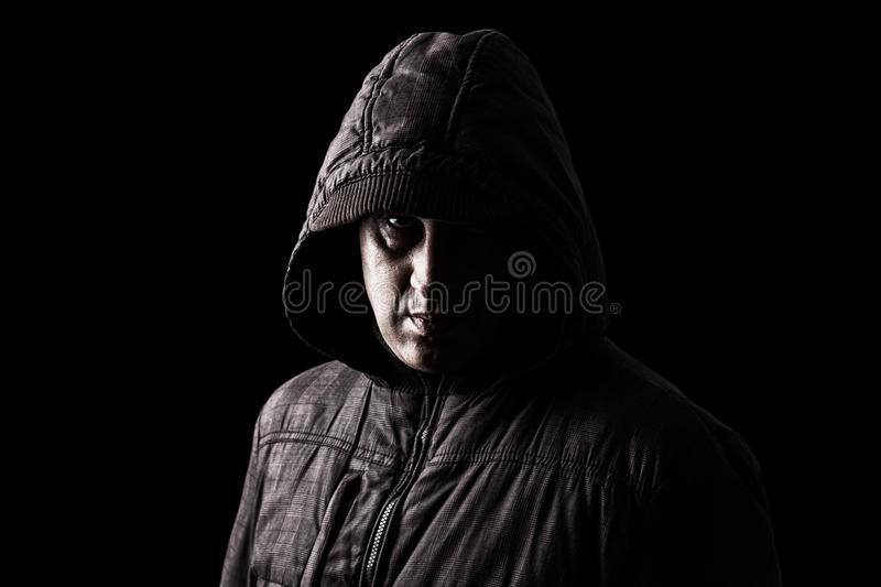 Scary Caucasian or white mature man hiding in the shadows stock photo