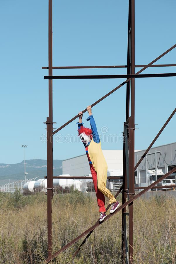 Scary clown on an abandoned billboard. A scary clown wearing a colorful yellow, red and blue costume outdoors, hanging from the rusty structure of an abandoned royalty free stock photography