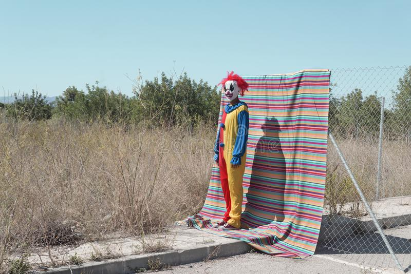 Scary clown standing outdoors. A scary clown, in a colorful yellow, red and blue costume, standing in front of a fence, with a colorful striped piece of cloth stock photography