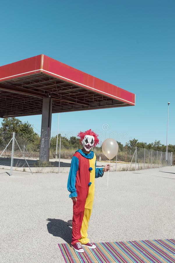 Scary clown with a golden balloon outdoors. A scary clown wearing a colorful yellow, red and blue costume, holding a golden balloon in his hand, in front of an stock images