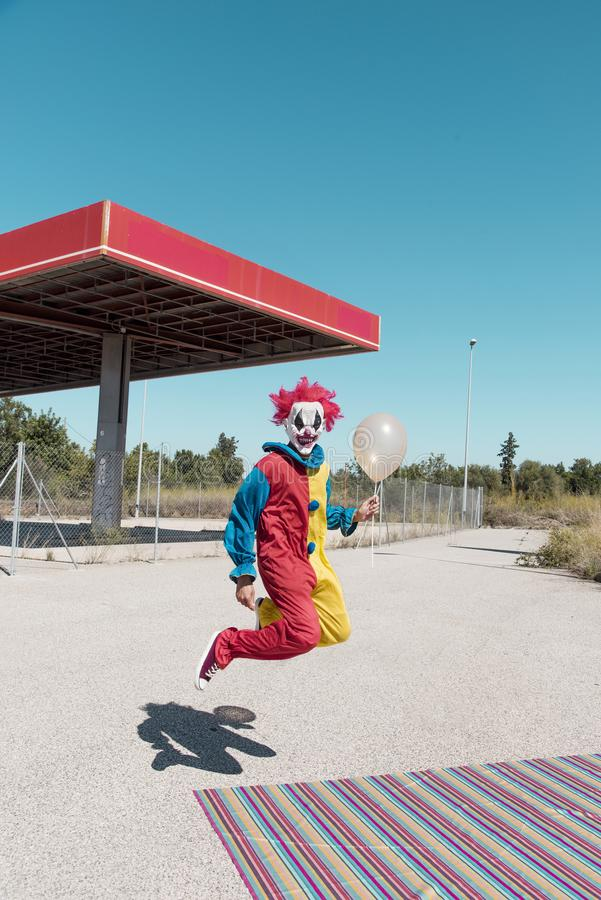 Scary clown with a golden balloon outdoors. A scary clown wearing a colorful yellow, red and blue costume, holding a golden balloon in his hand, jumping in front royalty free stock images