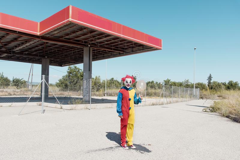 Scary clown with a golden balloon outdoors. A scary clown wearing a colorful yellow, red and blue costume, holding a golden balloon in his hand, in front of an stock image