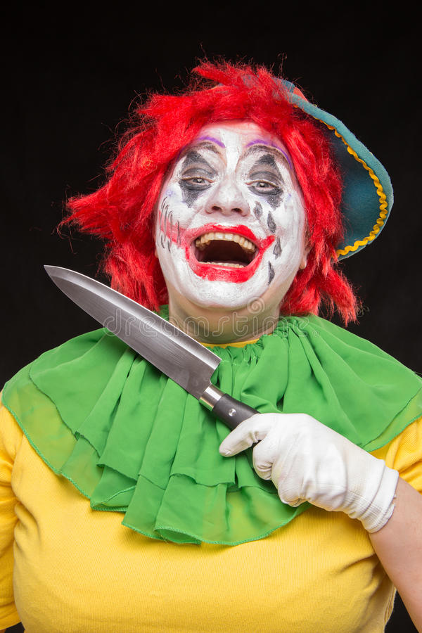 Download Scary Clown Joker With A Smile And Red Hair With A Big Knife On Stock Photo - Image of circus, creepy: 77379840
