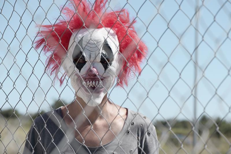 Scary clown outdoors. A scary clown looking with a threatening look through the wires of a fence royalty free stock photos