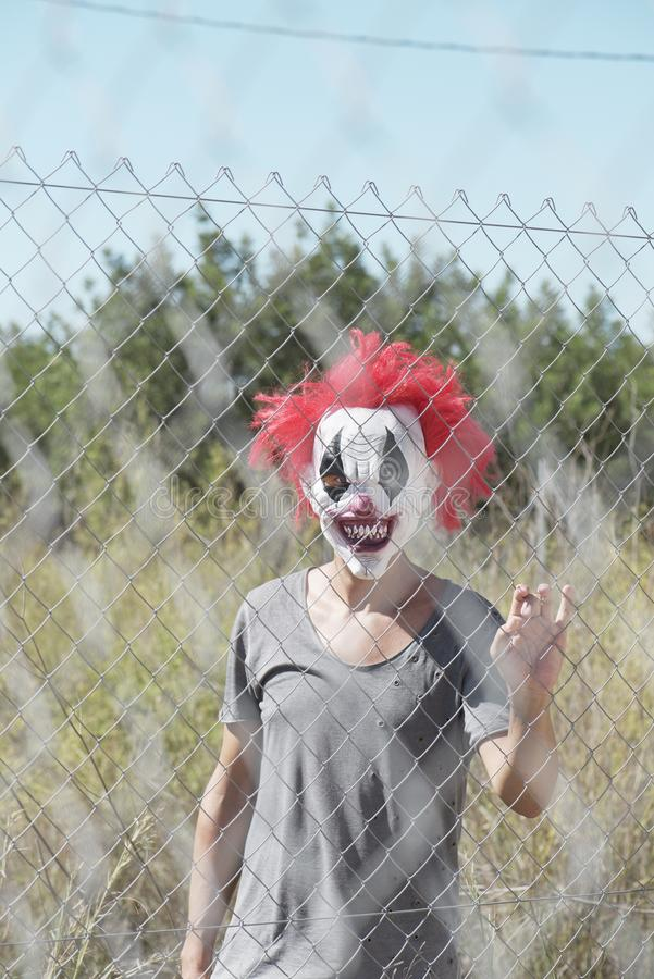 Scary clown behind a fence. A scary clown looking to the observer with a threatening look through the wires of a fence, in front of an abandoned natural stock photo