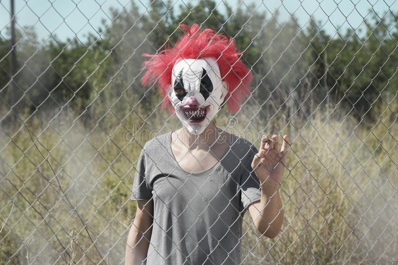 Scary clown behind a fence. A scary clown looking to the observer with a threatening look through the wires of a fence, in front of an abandoned natural stock photos