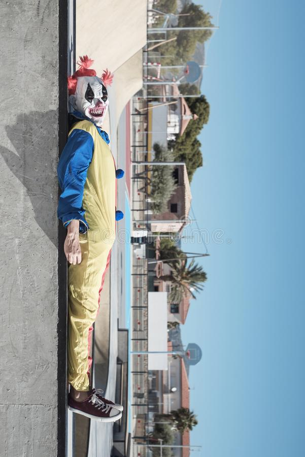 Scary clown lying down outdoors. A scary clown, wearing a colorful yellow, red and blue costume, lying down in an outdoor public sports complex stock photography