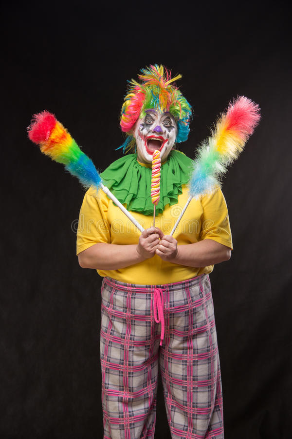 Scary clown with mohawk and a smile with a lollipop on a black b stock photo