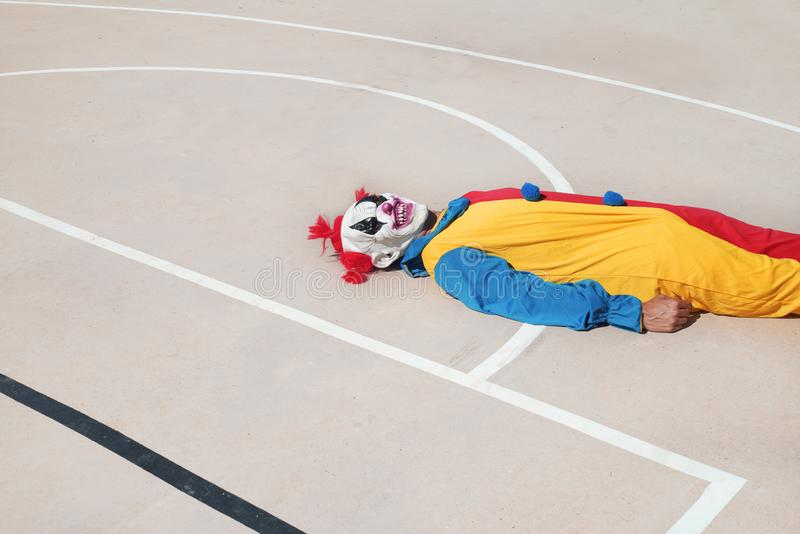 Scary clown on an outdoor basketball court. A scary clown, wearing a colorful yellow, red and blue costume, lying face up on an outdoor basketball court royalty free stock image