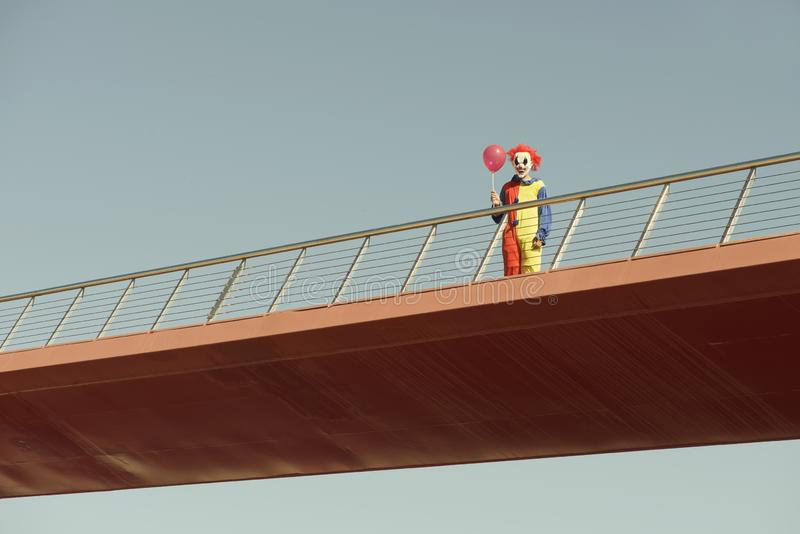 Scary clown with a red balloon on a bridge. A creepy clown wearing a colorful yellow, red and blue costume, holding a red balloon in his hand, standing in a stock image