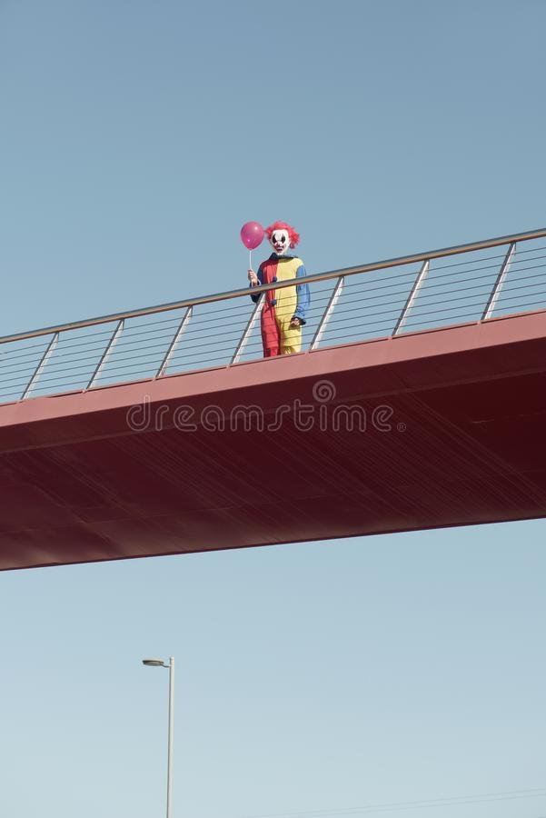 Scary clown with a red balloon on a bridge. A creepy clown wearing a colorful yellow, red and blue costume, holding a red balloon in his hand, standing in a royalty free stock photos