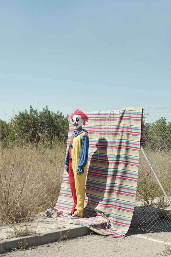 Scary clown standing outdoors. A scary clown, in a colorful yellow, red and blue costume, standing in front of a fence, with a colorful striped piece of cloth royalty free stock photography