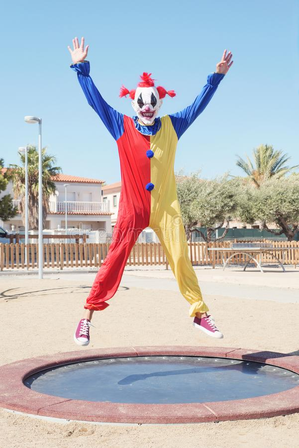 Scary clown jumping outdoors. A scary clown wearing a colorful yellow, red and blue costume bouncing on a trampoline in an outdoor public playground royalty free stock photos