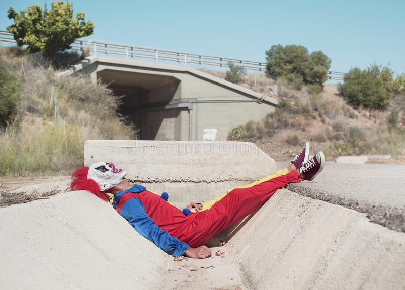 Scary clown outdoors. A scary clown, wearing a colorful yellow, red and blue costume, lying down face up on a gutter of a secondary road at the entrance to a stock photo