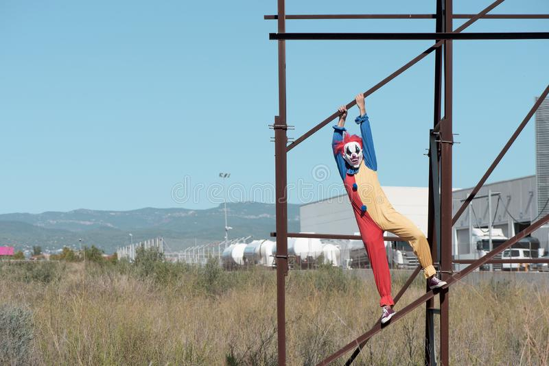 Scary clown on an abandoned billboard. A scary clown wearing a colorful yellow, red and blue costume outdoors, hanging from the rusty structure of an abandoned royalty free stock photos