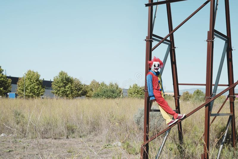 Scary clown on an abandoned billboard. A scary clown wearing a colorful yellow, red and blue costume outdoors, hanging from the rusty structure of an abandoned stock photo