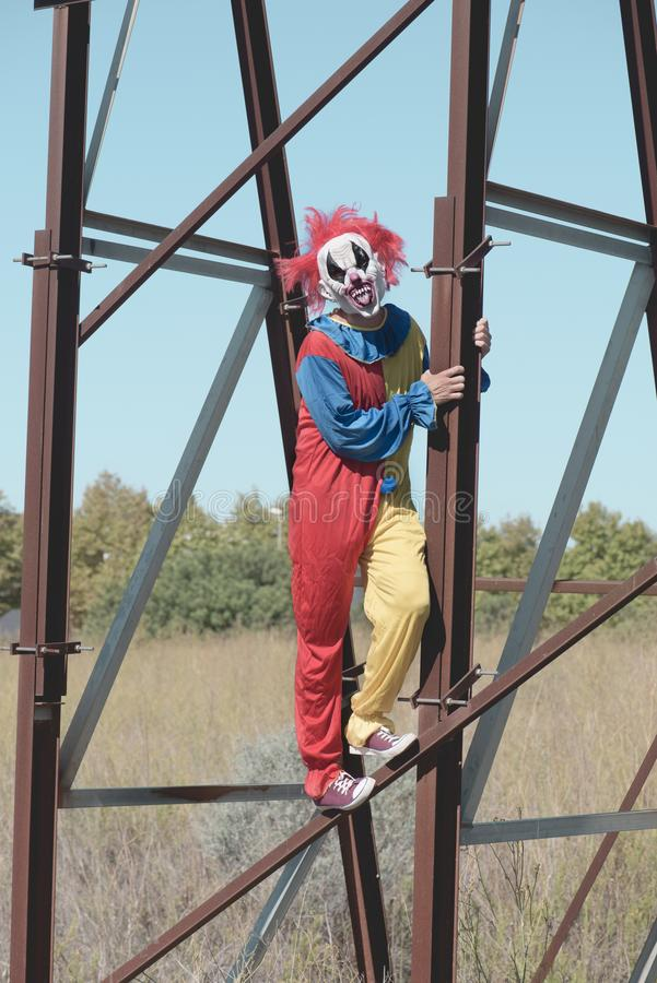 Scary clown sticking out his tongue outdoors. A scary clown, wearing a colorful yellow, red and blue costume outdoors, sticking out his tongue while hanging from royalty free stock photography