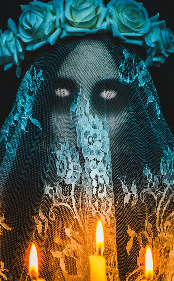 Scary corpse zombie bride with white empty eyes and candles on black background. Spooky halloween ghost character and concept of horror movies stock images